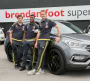 Three Wellington Phoenix players standing in front of a Hyundai Santa Fe Edition
