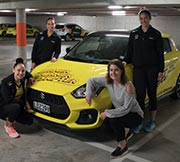 Pulse players standing in front of a Suzuki Swift Sport