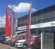 Brendan Foot Supersite Mitsubishi showroom with flags flying